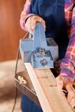 Carpenter Using Electric Planer On Wood. Midsection of female carpenter using electric planer on wood in workshop Stock Photos