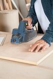 Carpenter Using Electric Planer On Wood. Midsection of carpenter using electric planer on wood at workshop Royalty Free Stock Image