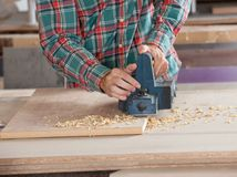 Carpenter Using Electric Planer On Wooden Plank. Midsection of male carpenter using electric planer on wooden plank at workshop Royalty Free Stock Photography