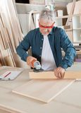 Carpenter Using Electric Sander At Table Stock Photo