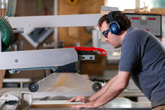 Carpenter using electric saw. Carpenter working on an electric buzz saw cutting some boards, he is wearing safety glasses and hearing protection to make things stock photography