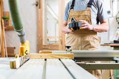 Carpenter using electric saw in carpentry. Carpenter working on an electric buzz saw cutting some boards royalty free stock photo