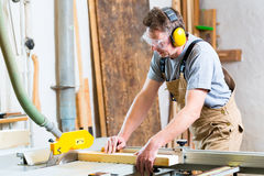 Carpenter using electric saw in carpentry. Carpenter working on an electric buzz saw cutting some boards, he is wearing safety glasses and hearing protection for stock photography