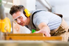 Carpenter using electric saw in carpentry. Carpenter working on an electric buzz saw cutting some boards, he is wearing safety glasses and hearing protection for royalty free stock photo