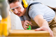 Carpenter using electric saw in carpentry. Carpenter working on an electric buzz saw cutting some boards, he is wearing safety glasses and hearing protection for stock image