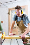 Carpenter using electric saw in carpentry. Carpenter working on an electric buzz saw cutting some boards, he is wearing safety glasses and hearing protection for royalty free stock photography
