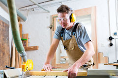 Carpenter using electric saw in carpentry. Carpenter working on an electric buzz saw cutting some boards, he is wearing safety glasses and hearing protection for royalty free stock photos