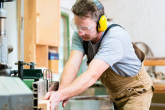Carpenter using electric saw in carpentry. Carpenter working on an electric buzz saw cutting some boards, he is wearing safety glasses and hearing protection for stock photo