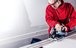 Carpenter using electric saw. Worker cut furniture board with electric saw Royalty Free Stock Image