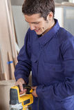 Carpenter using an electric saw Royalty Free Stock Photo