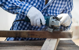 Carpenter using grinder on wood royalty free stock images