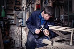Carpenter using Hammer and Chisel in Workshop. Portrait of Carpenter using Hammer and Chisel on a Wooden Window in his Workshop royalty free stock images