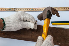 Carpenter is using hammer and nail on wood. On white background Stock Image