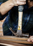 Carpenter using hammer pull a nail out from a wood Royalty Free Stock Photo