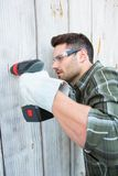 Carpenter using hand drill on wooden cabin Royalty Free Stock Photos