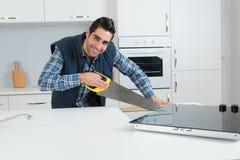 Carpenter using hand saw in kitchen. Carpenter using a hand saw in a kitchen Royalty Free Stock Images