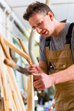 Carpenter using hand saw Stock Photos