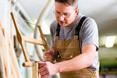 Carpenter using hand saw Stock Photos