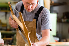Carpenter using hand saw Royalty Free Stock Photography