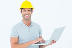 Carpenter using laptop  over white background Stock Photos