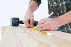 Carpenter using measure tape to mark on plank Royalty Free Stock Photography