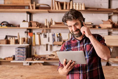 Carpenter using a mobile phone and holding digital tablet Royalty Free Stock Photo