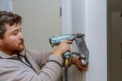 Free Carpenter Using Nail Gun To Moldings On Door, Framing Trim Royalty Free Stock Photo - 147199235
