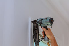 Carpenter using nail gun to moldings on windows, framing trim, Royalty Free Stock Photography