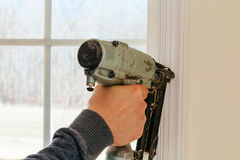 Carpenter using nail gun to moldings on windows, framing trim, Stock Images