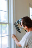 Carpenter using nail gun to moldings on windows, framing trim, Stock Photo