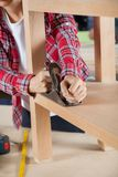 Carpenter Using Planer On Wooden Shelf Stock Images