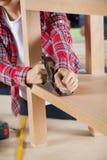 Carpenter Using Planer On Wooden Shelf. Midsection of female carpenter using planer on wooden shelf at workshop Stock Images