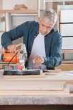 Carpenter Using Power Tool On Wood In Workshop. Senior male carpenter using power tool on wood in workshop Royalty Free Stock Photos