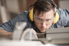 Carpenter using protective headphones. Carpenter while using electric tools wearing protective headphones Royalty Free Stock Photo