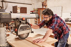 Carpenter using radial arm saw to cut wood in workshop. Skilled carpenter in his woodwork workshop, cutting a piece of wood with a radial arm circular saw, and Royalty Free Stock Photo