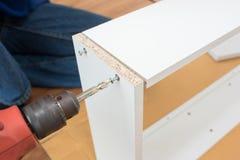 Carpenter using Screwdriver assemble furniture. On floor royalty free stock image