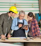 Carpenter Using Tablet Computer With Colleagues Royalty Free Stock Image