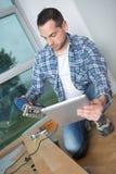 Carpenter using tablet to instal laminate flooring. Carpenter using a tablet to instal a laminate flooring stock photos