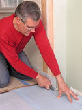 Carpenter using utility knife. Carpenter cutting underlayment with utility knife Royalty Free Stock Image