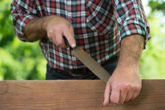 Carpenter using a wood rasp on the edge of a board Royalty Free Stock Photos