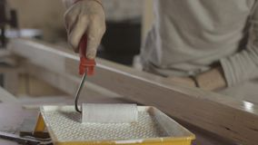 Carpenter varnishing long wooden board by paint roller. Process of treatment. Furniture. Close up stock video