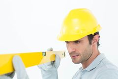 Carpenter wearing hard hat while using spirit level Stock Photo
