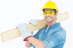 Carpenter wearing hardhat and glasses while carrying wooden planks Stock Image