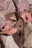 Carpenter weaves straw Stock Photo