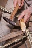 Carpenter weaves straw Stock Images