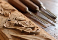 Carpenter wood chisel tool with carving on old weathered wooden workbench Royalty Free Stock Image