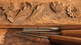 Carpenter wood chisel tool with carving on old weathered wooden workbench Stock Image