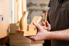 Carpenter with wood planer and hammer. Carpenter working with a planer in his workshop, close up on the tool with hands Royalty Free Stock Photo