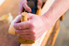Carpenter with wood planer and workpiece in carpentry Stock Photography