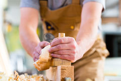 Carpenter with wood planer and workpiece in carpentry Stock Photos